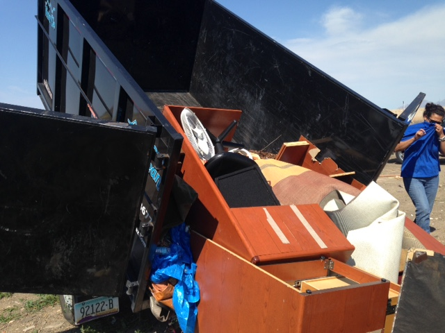 unusable desk and office file cabinets being dumped at landfill